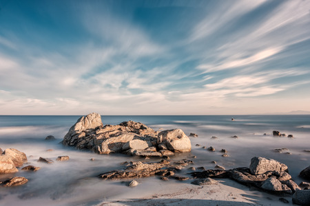 Long exposure image of Mediterranean sea washing over rocks and onto sandy beach at sunrise near Ile Rousse in Corsica