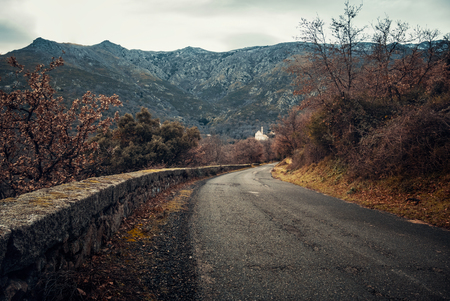 Tarmac road bordered by a low stone wall leading to the village and church of Ville di Paraso in the mountains of the Balagne region of Corsica