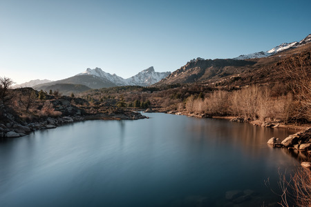 River Golo with the village of Albertacce in the distance and snow capped Paglia Orba mountain in central Corsica Stock Photo