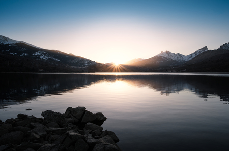 Sun setting behind snow capped mountains behind a calm Lake Calacuccia in central Corsica Stock Photo