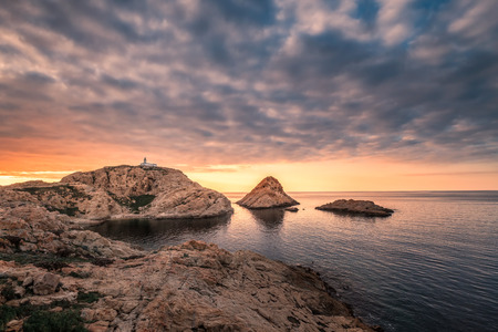 Sun setting behind the lighthouse on La Pietra rock at Ile Rousse in the Balagne region of Corsica
