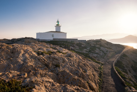 Early morning sun on the lighthouse at La Pietra rock in Ile Rousse in the Balagne region of Corsica Stock Photo