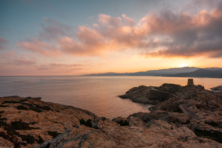Sunrise over the Genoese tower at La Pietra rock in LIle Rousse in the Balagne region of Corsica with the hills of the Desert des Agriates in the distance