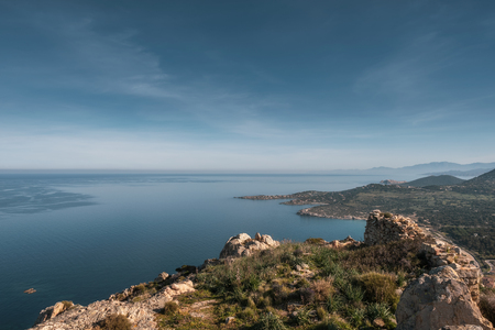 Coastline of the Balagne region of Corsica and calm Mediterranean sea viewed from a rocky outcrop in the hills above the village of Algajola