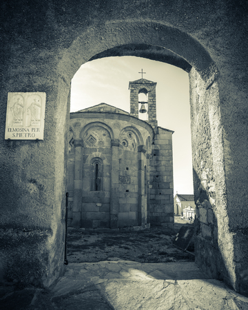 Black and white image of stone archway entrance to 11th Century San Pietro and San Paolo Roman chapel and surrounding graveyard at Lumio in the Balagne region of Corsica.