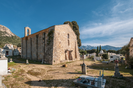 11th Century San Pietro and San Paolo Roman chapel and surrounding graveyard at Lumio in the Balagne region of Corsica with snow capped mountains in the distance.