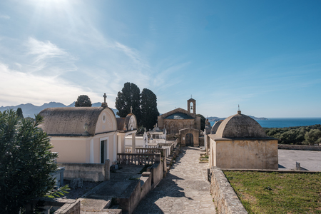 11th Century San Pietro and San Paolo Roman chapel and surrounding graveyard at Lumio in the Balagne region of Corsica with Mediterranean sea in the distance Stock Photo
