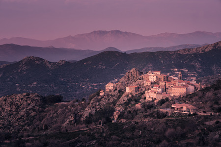 Purple glow of dusk on the mountain village of Speloncato in the Balagne region of Corsica with mountains in the distance