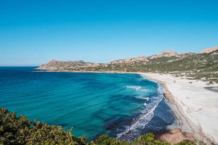 Deserted sandy beach and turquoise Mediterranean sea at Ostriconi in the Balagne region of Corsica under a clear blue sky