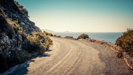 Old tarmac road at Ostriconi in the Balagne region of Corsica with view over the Mediterranean sea towards Ile Rousse Stock Photo