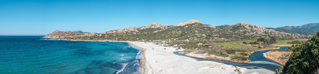 Panoramic view over a deserted sandy beach and turquoise Mediterranean sea at Ostriconi in the Balagne region of Corsica under a clear blue sky