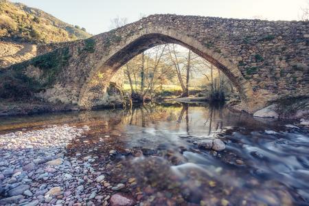 Antiguo puente de piedra genovés sobre el rápido río Tartagine en Piana en la región de Córcega Balagne
