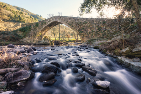 Ancient Genoese stone bridge over the fast flowing Tartagine river at Piana in the Balagne region of Corsica Stock Photo