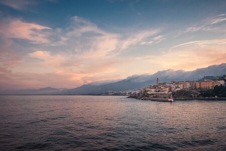 Dusk falling over the port and old town of Bastia in northern Corsica with cliud covered mountains in the distance Banco de Imagens