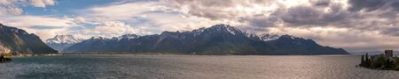 Panoramic view of dramatic evening clouds over Lake Geneva in Switzerland with snow capped mountains in the distance Banco de Imagens