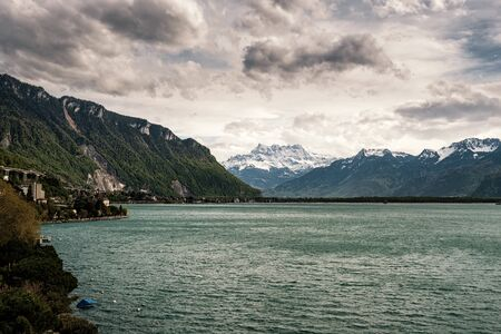 Dramatic evening clouds over Lake Geneva in Switzerland with snow capped mountains in the distance