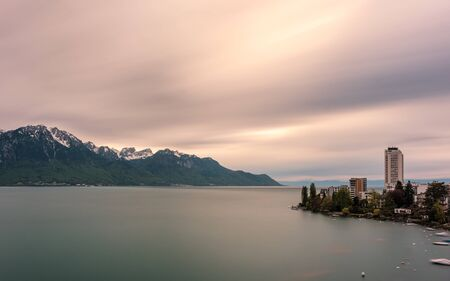 Long exposure image of dramatic evening clouds over snow capped mountains behind Lake Geneva from Luasanne in Switzerland