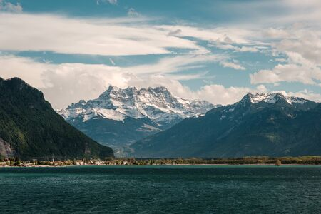 Dramatic evening clouds over snow capped mountains of Cime de lEst, Haute Cime and Mont Ruan behind Lake Geneva in Switzerland Banco de Imagens