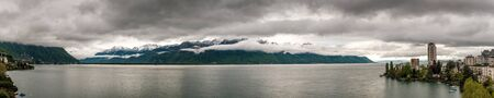 Panoramic view of dramatic morning clouds over Lake Geneva from Laussane in Switzerland with snow capped mountains in the distance Banco de Imagens