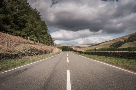 White lines down the centre of a tarmac road lined by dry stone walls at the foot of Woodhead Pass in the countryside of Derbyshire with fields, trees and hills in the distance