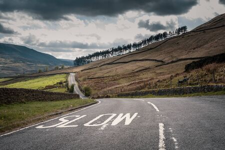 White Slow warning sign painted on a winding rural tarmac road in the countryside of Derbyshire with fields, trees and hills in the distance