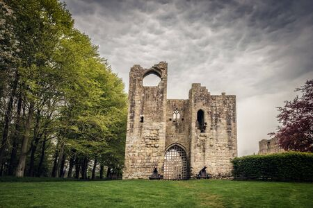 Dark storm clouds gather over the dramatic ruins of the medieval fortification of Etal Castle in Northumberland, England
