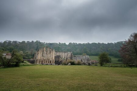 Dark clouds hang over the 11th Century ruins of Rievaulx Abbey, one of Englands largest Cistercian Monasteries, in the North York Moors Banco de Imagens