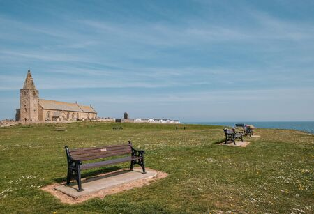 Four park benches looking out to sea at Newbiggin by the Sea in Northumberland with St Bartholomews Church and the Newbiggin time capsule monument  in the distance under a blue sky