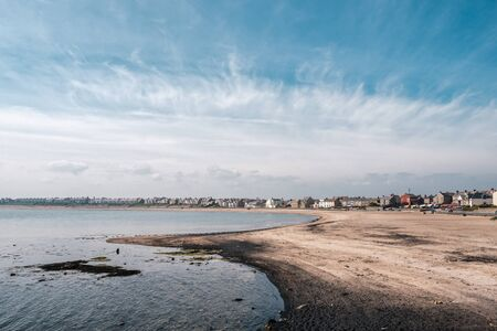Rows of houses along the sea front at Newbiggin by the sea in Northumberland with a sandy beach in the foreground on a bright sunny day