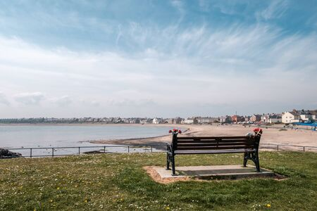 Park bench looking out to sea at Newbiggin by the Sea in Northumberland with rows of houses along the beach front  in the distance under a blue sky