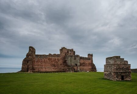 The 14th century fortress of Tantallon castle in East Lothian in Scotland with the Firth of Forth in the distance and an ancient pigeon house in the foreground Banco de Imagens