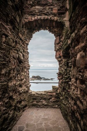 View of the rocky coastline and Firth of Forth through and ancient stone window in the remains of the 14th century Tantallon Castle in East Lothian in Scotland