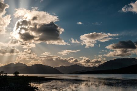 Late afternoon sun rays filtering through the clouds over Loch Linnhe in Scotland with mountains silhouetted in the distance Stock Photo