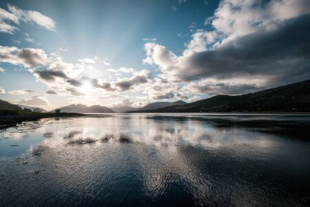 Late afternoon sun rays filtering through the clouds over Loch Linnhe in Scotland with mountains silhouetted in the distance Banco de Imagens