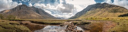 Panoramic view of the sky reflected in a stream of water in front of Loch Etive in the Highlands of Scotland with mountains either side