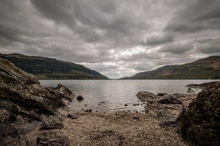 Rocks on a pebble beach on the shoreline of Loch Lomond in Scotland with dark clouds overhead Banco de Imagens