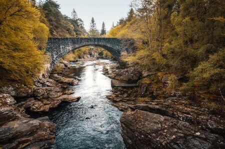 Golden trees surround the road bridge over the Moriston River at Invermoriston in Scotland with a small stone building in the distance