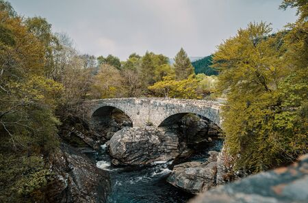 Thomas Telford bridge built in 1831 over the Moriston River at Invermoriston in Scotland surrounded by woodland