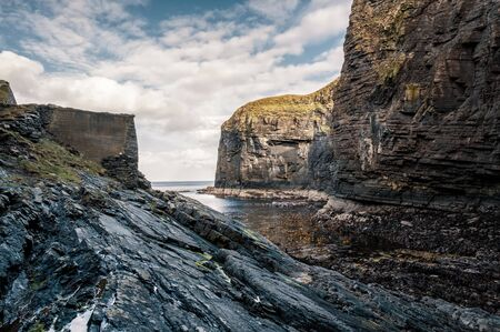 Steep cliffs and rocks protect the entrance to Whaligoe Harbour near Wick in Caithness in Scotland Banco de Imagens