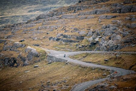 Lone motorcyclist descends Healy Pass as it winds its way down the valley on the Beara peninsula in County Cork in Ireland