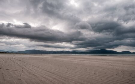 Dark clouds over the large sandy beach and distant hills of Inch Beach on the Dingle Peninsula in the south west of Ireland Stok Fotoğraf