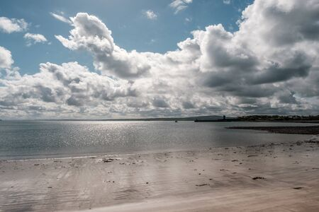 Sun glistening on the sandy beach and calm sea overlooking Carrigaholt Castle in County Clare in Ireland 写真素材