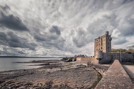 Dark clouds hang over the ruins of Carrigaholt Castle which overlooks the Shannon Estuary in County Clare in Ireland