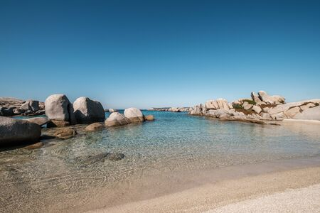 Large granite boulders and sandy beach on the coast of Cavallo Island n the Lavezzi archipelago of Corsica 免版税图像