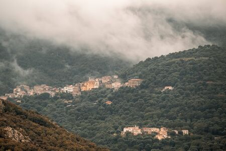 The ancient mountain villages of Muro and Poggiali in the Balagne region of Corsica under dark storm clouds