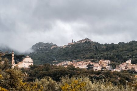 The ancient mountain villages of Ville di Paraso and Speloncato in the Balagne region of Corsica under dark storm clouds