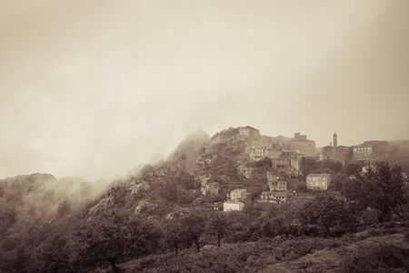 Sepia image of the ancient mountain village of Speloncato shrouded in mist in  in the Balagne region of Corsica 版權商用圖片 - 134808189