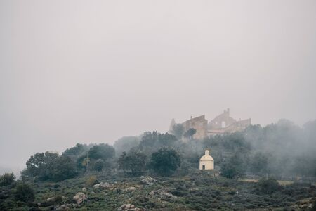 The ancient Couvent Santa Maria di a Pace and a mausoleum shrouded in mist in the ancient mountain village of Speloncato in the Balagne region of Corsica