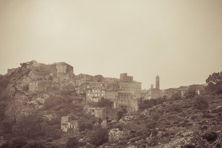 Sepia image of the ancient mountain village of Speloncato shrouded in mist in  in the Balagne region of Corsica 版權商用圖片 - 134808216