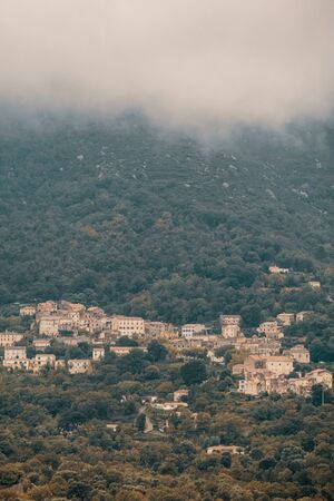 The ancient mountain village of Feliceto in the Balagne region of Corsica under dark storm clouds